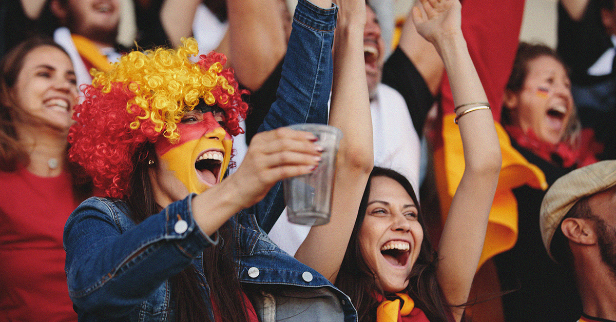 Women cheering at sports game with face paint and wig